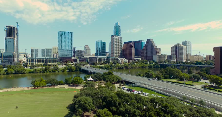 The camera starts at a low altitude but gains height as it approaches the Austin, Texas skyline on a bright beautiful day.  Traffic and pedestrians populate the streets and sidewalks. | Shutterstock HD Video #12730391