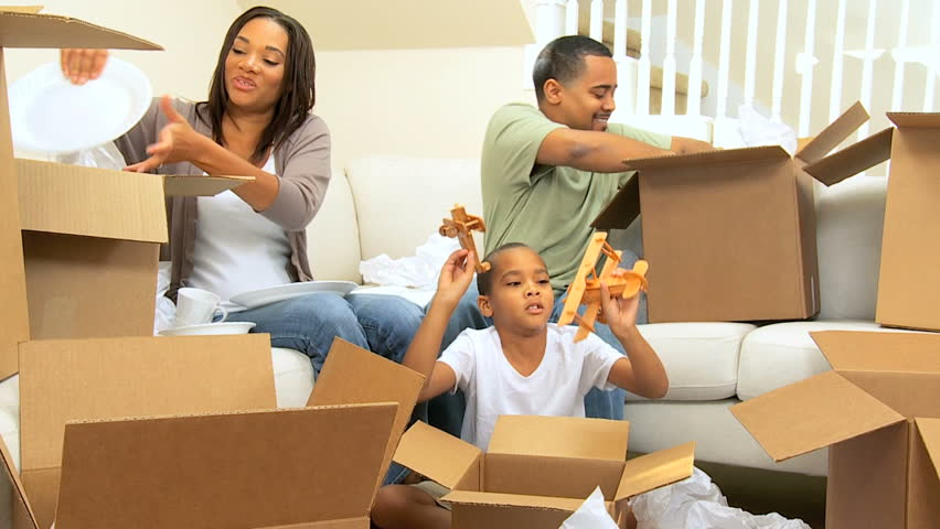 African american family surrounded by packing tissue paper from unpacking boxes