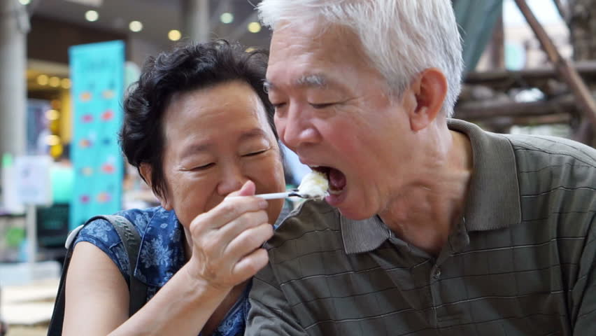 Asian senior couple eating an ice cream and feed each other abstract eternal love