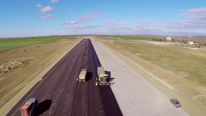 Tracked paver laying fresh asphalt pavement on an airport runway, aerial view