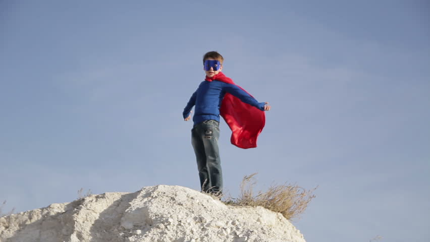 superhero boy  runs through the mountains and trying to fly
