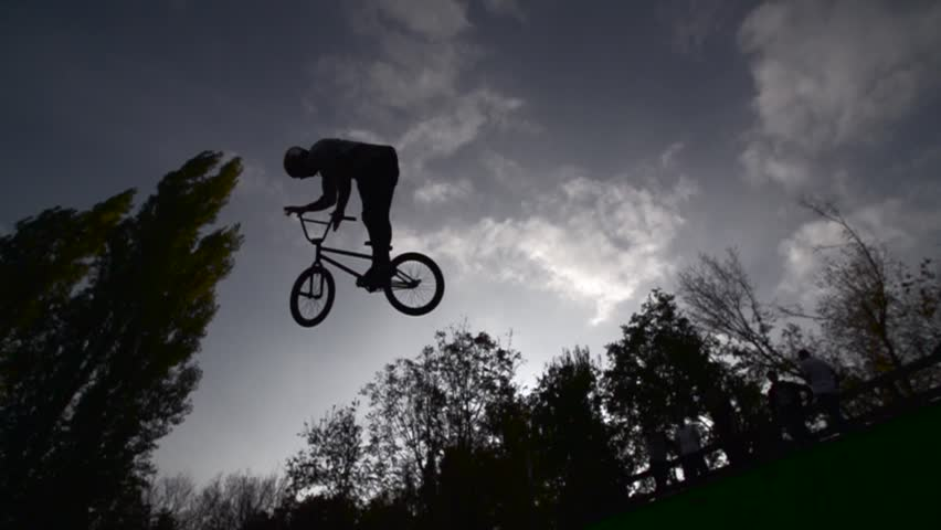 Silhouette of jumper, performing BMX mountain bike sport jump. Slow Motion 400 fps #12771932