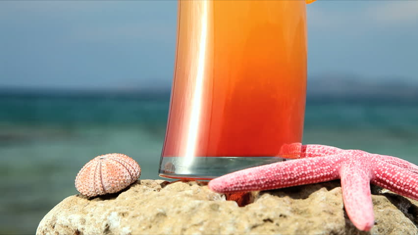 close up of cocktail down the beach, tilt shot