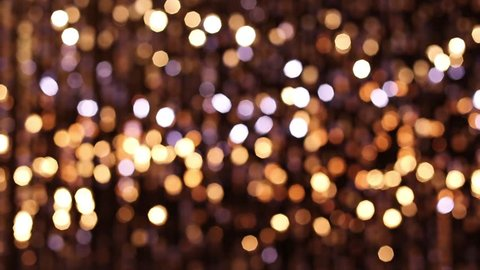 Abstract glittering lights, gold background, a real shot video in the blur
