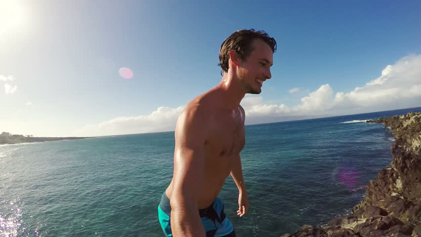 POV Slow Motion Cliff Jumping Backflip. Athletic Young Man Jumping From Cliff Into Ocean. Adventure Extreme Sports Lifestyle Hobby Vacation