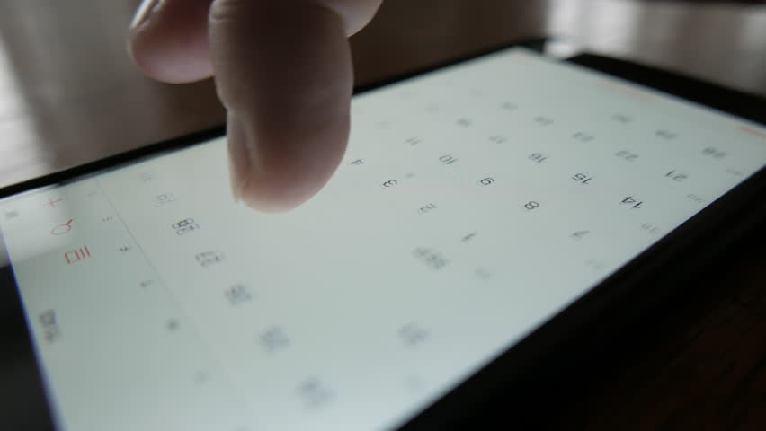 Close-up of a smartphone (iPhone), finger scrolls through calendar looking for the right date. To confirm a meeting or an appointment.