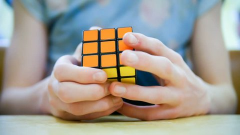London, England - April 29, 2014: Young Person solving a Rubik's Cube puzzle, Rubik's Cube is a 3-D combination puzzle invented in 1974 by Hungarian sculptor and professor of architecture Ern? Rubik.