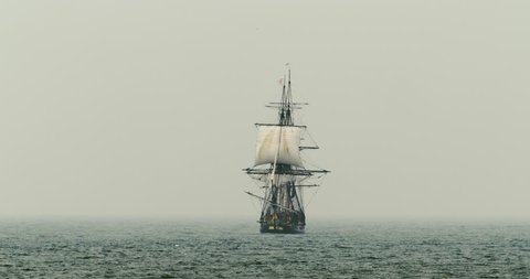 A tall ship schooner sails on the high seas in misty fog.