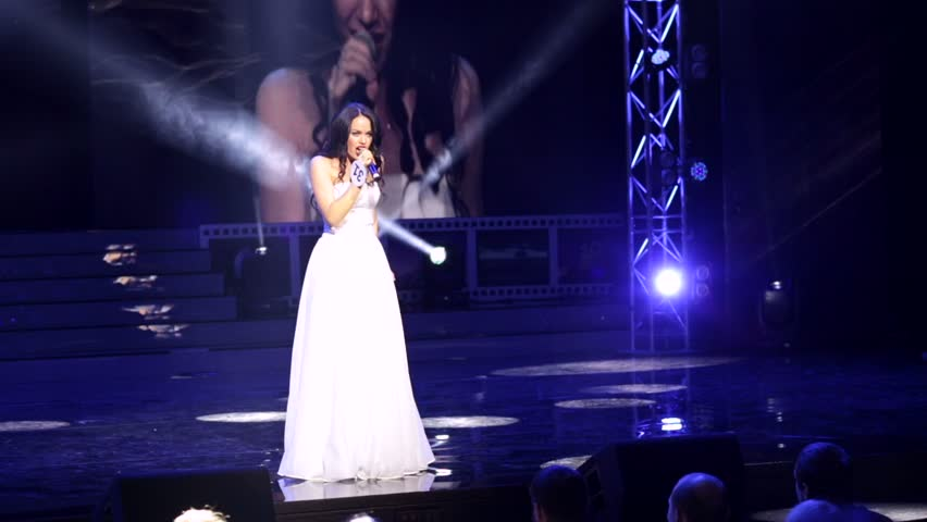 """MOSCOW, RUSSIA - NOVEMBER 18, 2015: Woman in a white dress sings on a stage during an annual national pageant  """"Krasa Rossii"""" (The Beauty of Russia)."""