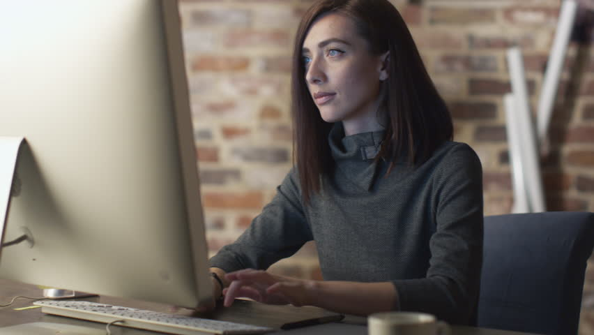 Young brunette woman is working in front of a monitor in a loft. Shot on RED Cinema Camera in 4K (UHD).