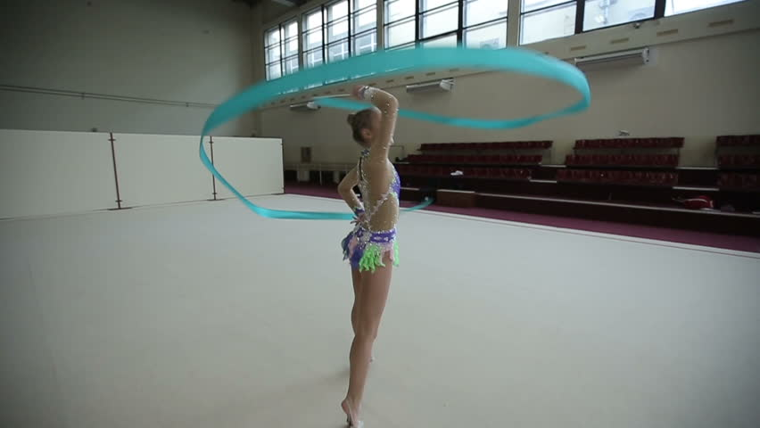Girl training a gymnastics exercise with a ribbon. Slow motion