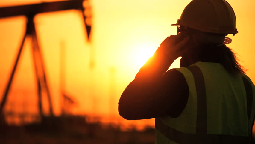 Female engineer using a cell phone overseeing the site of crude oil production at sunset