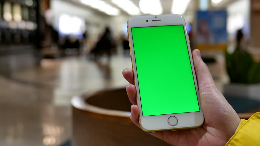 Coquitlam, BC, Canada - November 25, 2015 : 4k of woman holds a blank smart device with a green screen for your own custom content in front of apple store