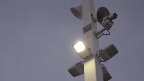 Cameras surveillance,dusk,dystopian future.A big pole with surveillance camera megaphones,speakers and halogen lights placed perimetrical looking down in dusk backcground.
