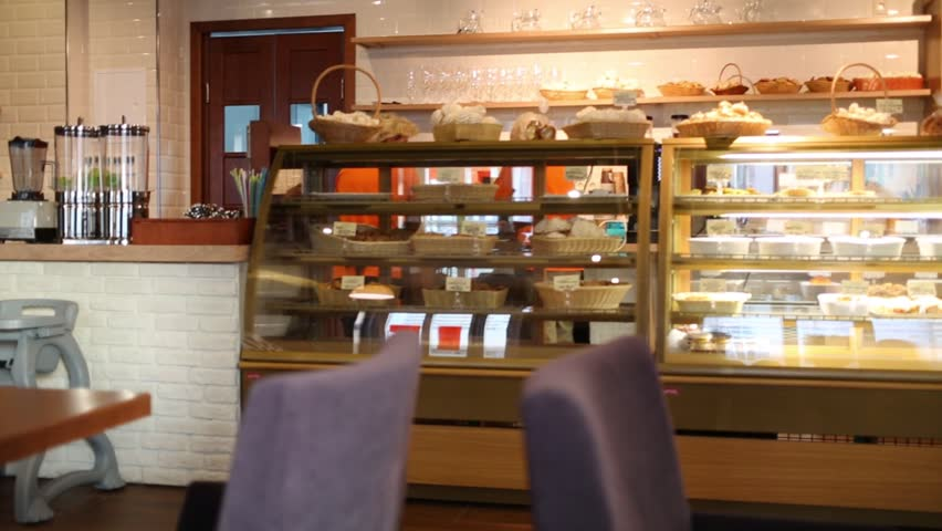 Interior of small cafe with showcase with sweets and pastries