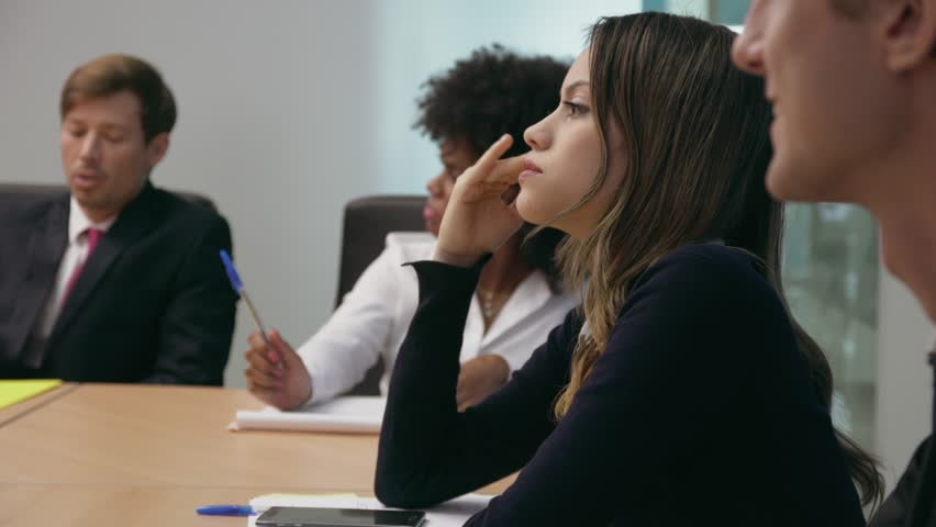 Group of business people during meeting in corporate conference room. A woman gets a headache and touches her temples. Medium shot