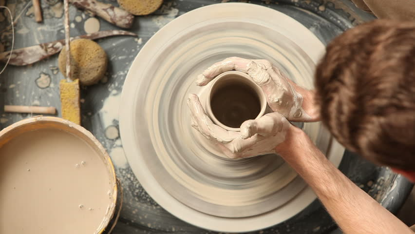Cinemagraph - Overhead view of man making pot on pottery wheel. Looping Motion Photo.