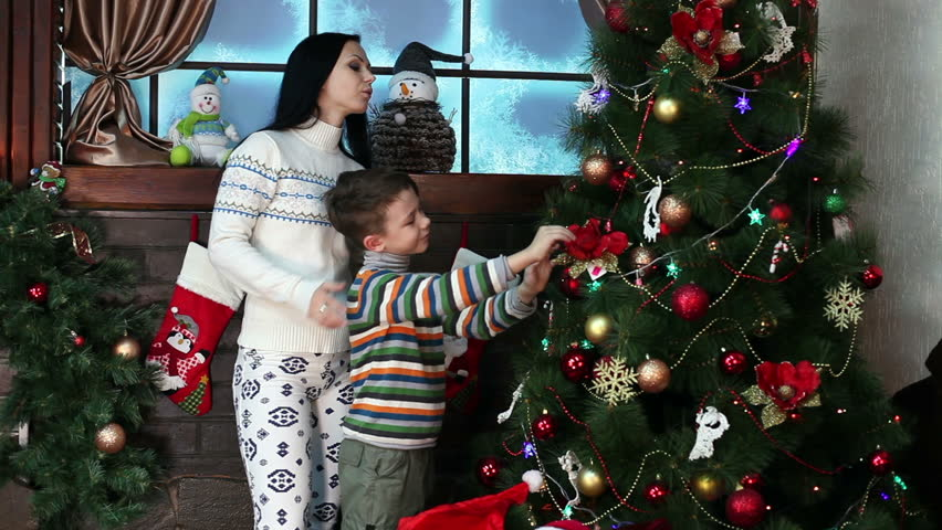 Beautiful woman with a child decorate the Christmas tree, accepts gifts, sit by the fireplace and read a book. New Year. Christmas. Christmas toys, garlands, festive mood. | Shutterstock HD Video #13102592