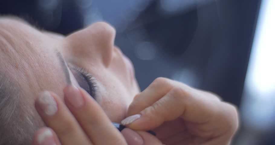 Beautician, Female Stylist is Applying a Makeup, Eyeshadows for a Woman, Model, Client is Sitting in a Chair with Her Eyes Closed, Face Close Up top down, beautician hands close up, painted nails, | Shutterstock HD Video #13137710