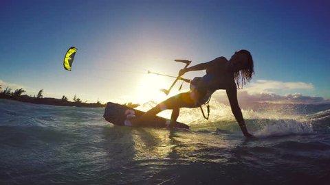 Extreme Kitesurfing at Sunset. Summer Ocean Sport in Slow Motion. Girl Kite Surfing in Bikini