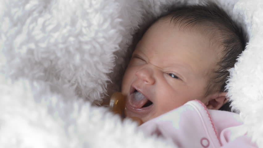 Cute little girl close up of newborn girl showing emotion newborn baby maternity concept