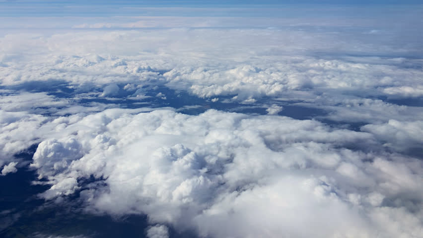 Traveling by air above clouds. View through an airplane window. Flying over the Mediterranean Sea through cirrus and cumulus clouds and little turbulence, showing Earth's atmosphere. | Shutterstock HD Video #13190072