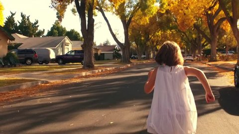 Happy 5 year old girl child in white dress running away from POV camera on autumn city street. Slow motion.