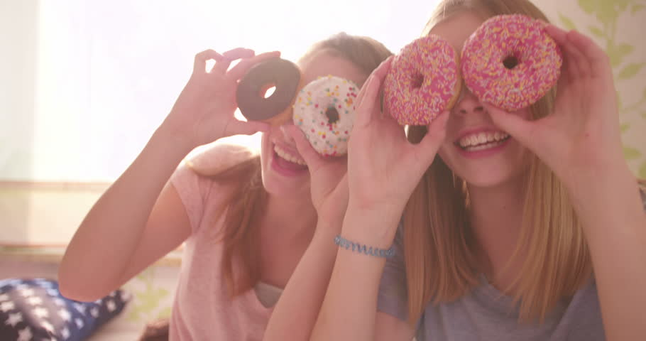 Two adolescent girl friends having a pyjama party in a sunny bedroom holding colourful doughnuts up to their faces to cover their eyes while sticking out their tongues at the camera