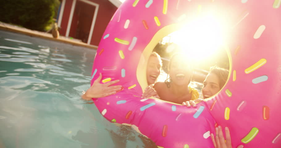 Three girls floating in a swimming pool with a pool inflatable looking like a big pink donut having fun while laughing on a summer afternoon in a backyard with sunflare