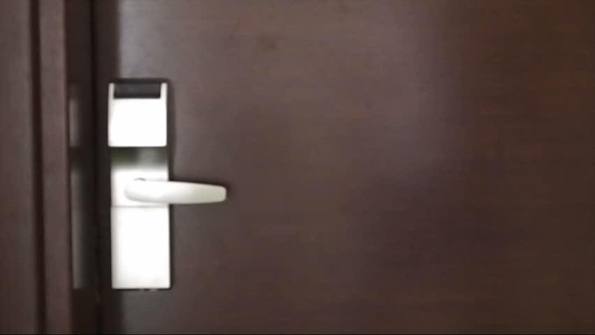 Young man entering hotel room door