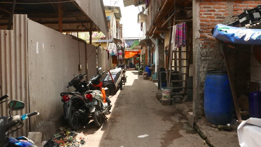 JAKARTA, INDONESIA - MARCH 09, 2015: POV go through slum, first person view move through narrow passage. Hovels at Sunda Kelapa harbor area and Pasar Ikan, fish market surroundings