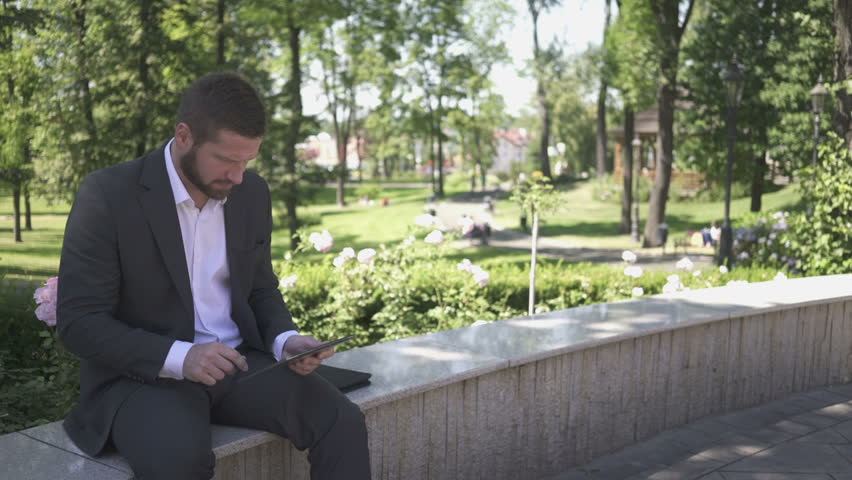 Businessman sitting on wall against park, takes selfie by tablet, pan shot, left.