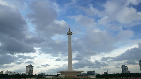 JAKARTA, INDONESIA - MARCH 08, 2015: Dark clouds are gathering over the National Monument, Jakarta, long time-lapse shot. Symbolic tower, city landmark, located at huge Merdeka Square