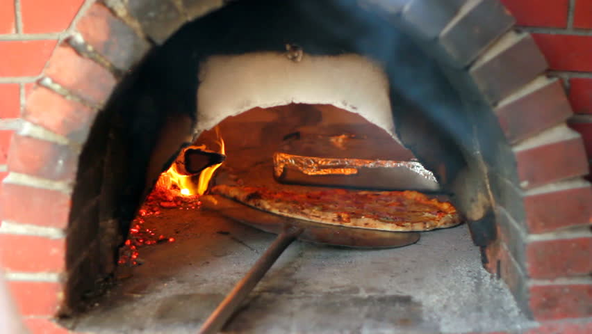 Pizza being baked in traditional wood burning pizza-bread oven in a restaurant. Chef making pizza in commercial kitchen. Pizza Place. Food Preparation. Pizza Chef.