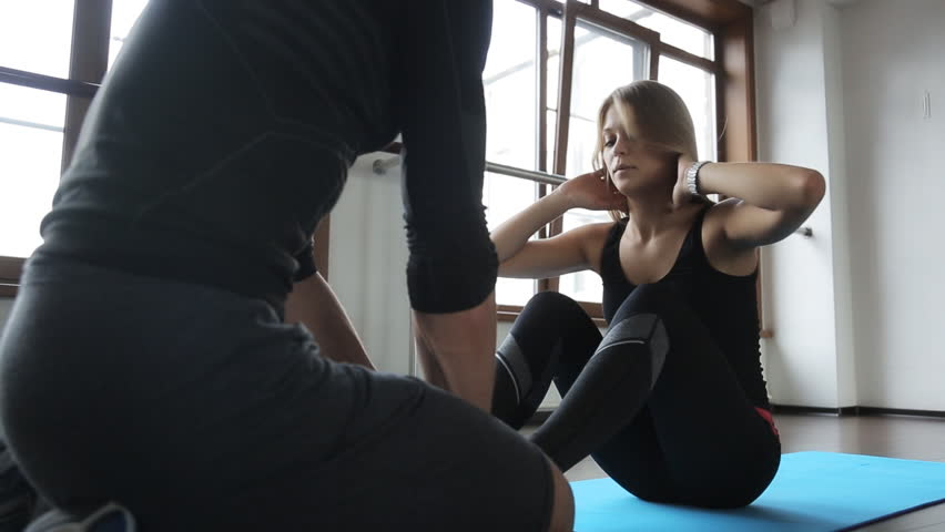 attractive girl athlete engaged in exercises on work abdominal, the press shakes. Helps her in this her own personal trainer of fitness man in a tracksuit, he holds her ankles
