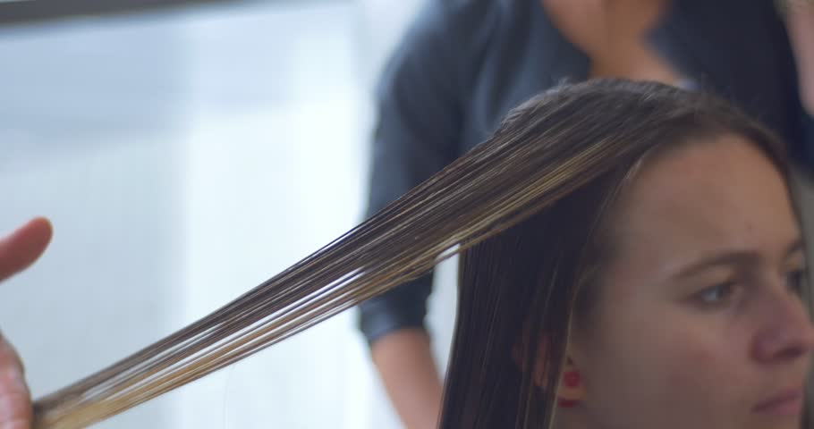 Man Stylist, Hairdresser Combs And Cuts The Client's Hairs, Making The Hairstyle For a Woman with Long Hairs, concentrated face, model is worn in salon dressing gown, hairdresser's hands close up,