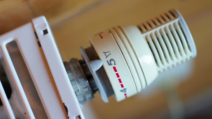 Hand of a man turning thermostat regulator radiator in the house. | Shutterstock HD Video #13263332
