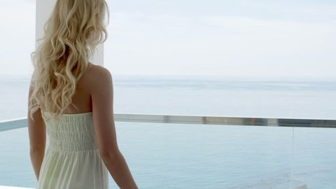 Rear View of Blond Woman Wearing Long Strapless Summer Dress Leaning on Railing of Glass Balcony Overlooking Ocean