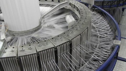 Textile industry - yarn spools on spinning machine in a factory