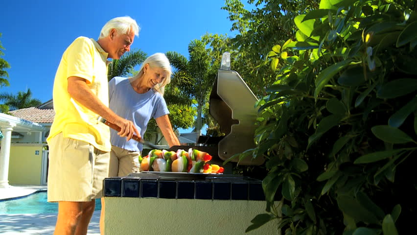 Senior couple enjoying a healthy eating lifestyle grilling delicious fresh food on a barbecue outdoors filmed at 60FPS