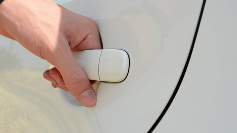 somebody opens and closes door of modern car - focus on door handle