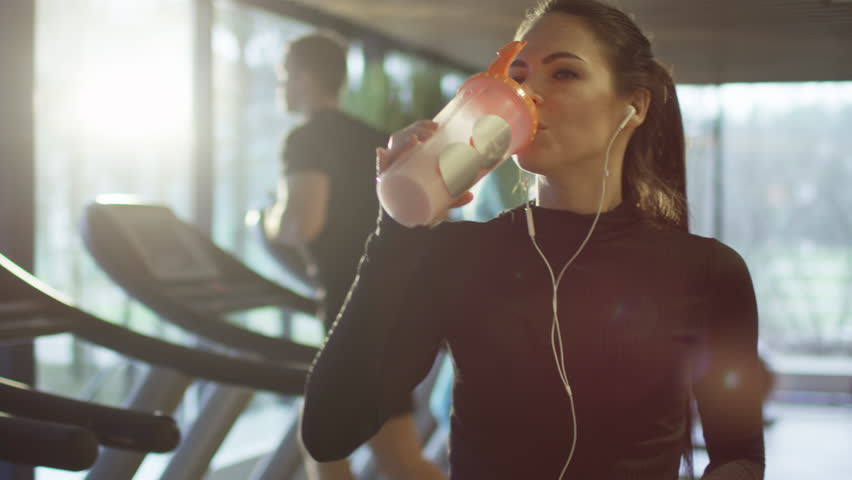 Attractive caucasian girl is drinking a protein shake drink next to a treadmill in the sport gym. Shot on RED Cinema Camera in 4K (UHD). | Shutterstock Video #13390028