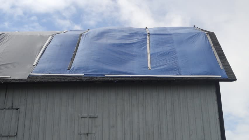 rippling and billowing of blue plastic tarpaulin on pitched barn roof under repair on a windy