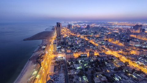 Cityscape of Ajman from rooftop from night to day transition timelapse. Ajman is the capital of the emirate of Ajman in the United Arab Emirates. 4K