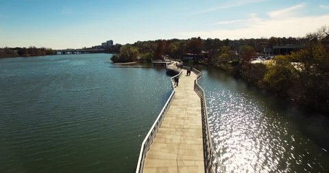 Bicyclists and pedestrians are seen walking along the boardwalk in Austin, Texas on a beautiful fall day.