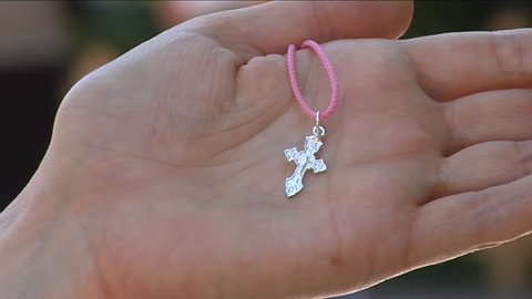 Male Hand is Holding a Childish Silver Cross on a Pink Cord Close Up People at Ritual of Christening of The Child in Orthodox Church People on Background, washing of sacred water, wearing of the