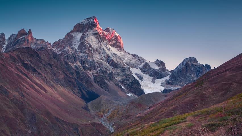 Time lapse clip. Colorful sunrise on the Ushba peak in the Caucasus mountains. Upper Svaneti, Georgia, Europe. 4K video (Ultra High Definition).