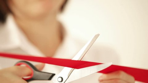 Business woman cutting the red ribbon with scissors and opens the event