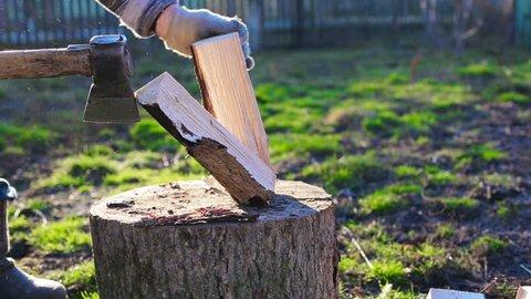A man chops wood. Sunny