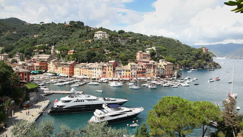 City view of the famous village of Portofino and its port with boats and sailboats, Italy. Two shots, sequence